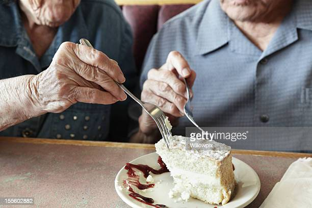grandpa and grandma sharing cake - cake stock pictures, royalty-free photos & images