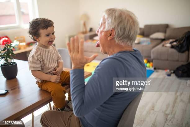 nonno e nipote si godono il loro tempo di gioco a casa - 2 3 anni foto e immagini stock