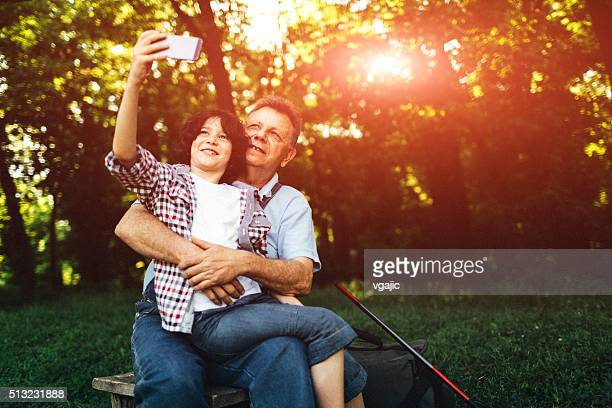 Grandpa and grandson fishing together and making selfie.