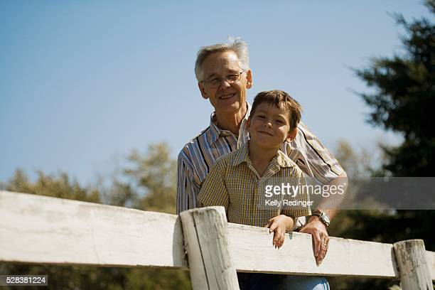 Grandpa and grandson outside leaning on fence