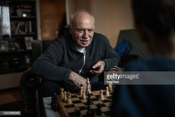 grandpa and grandson playing chess - chess stock pictures, royalty-free photos & images