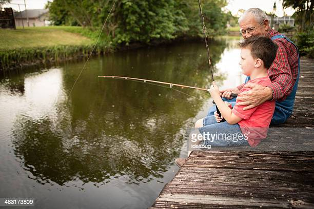Grandpa and His Grandson Fishing From Dock, Side View