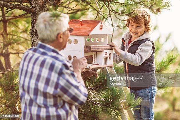 Grandpa and his grandson installing a birdhouse