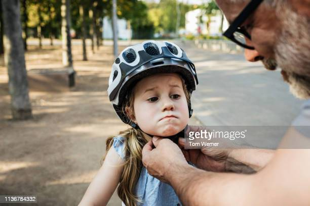 grandpa doing up granddaughter's crash helmet - sportschutzhelm stock-fotos und bilder