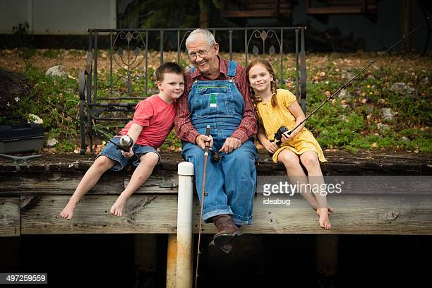 grandpa fishing with his great grandchildren - great granddaughter stock photos and pictures