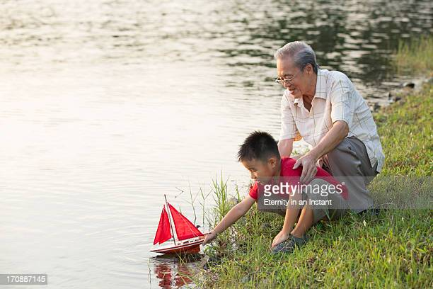 Grandpa helping grandson with model boat by lake
