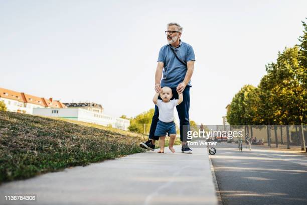 grandpa holding grandson's hands while they walk - gemeinsam gehen stock-fotos und bilder