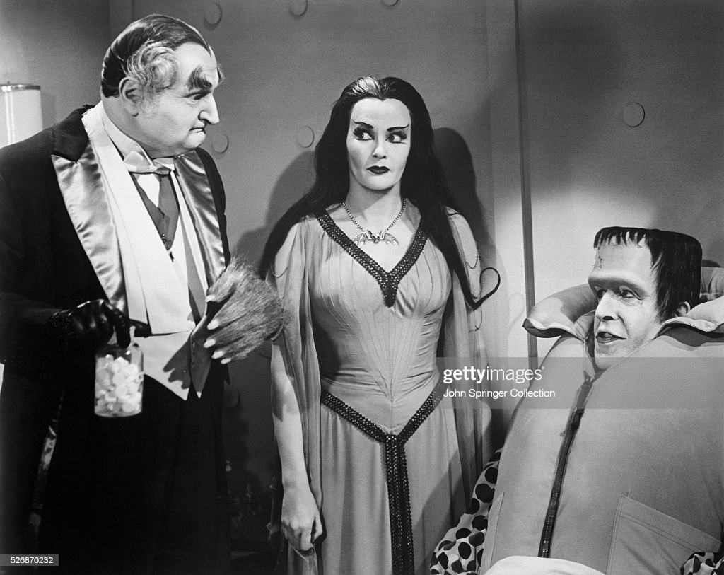 Grandpa (Al Lewis) holding pills, Lily (Yvonne De Carlo) eyeing Grandpa, and Herman (Fred Gwynne) wearing a life vest during an episode of The Munsters.