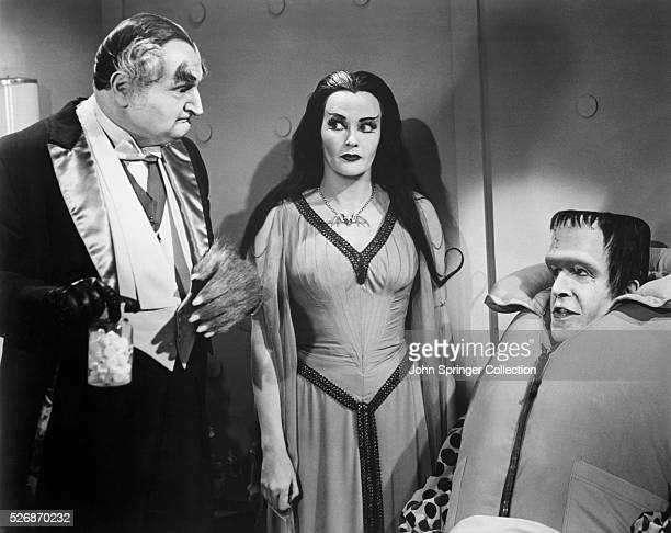Grandpa holding pills Lily eyeing Grandpa and Herman wearing a life vest during an episode of The Munsters
