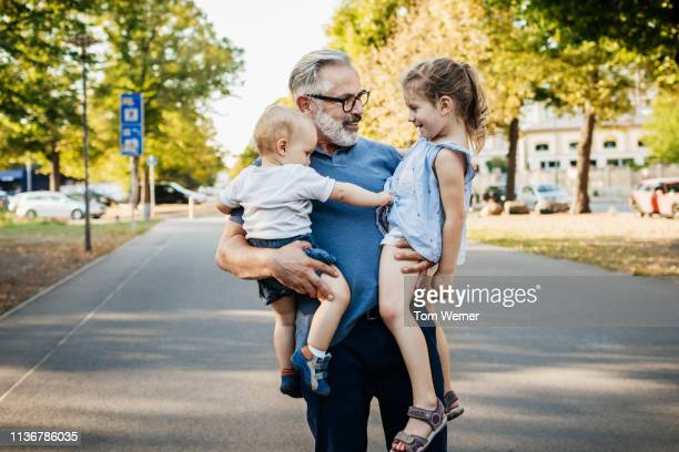 grandpa holding two grandchildren at the park - innocence stock pictures, royalty-free photos & images