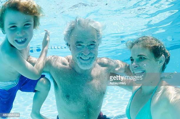 Grandpa, mother, and son swimming together, underwater
