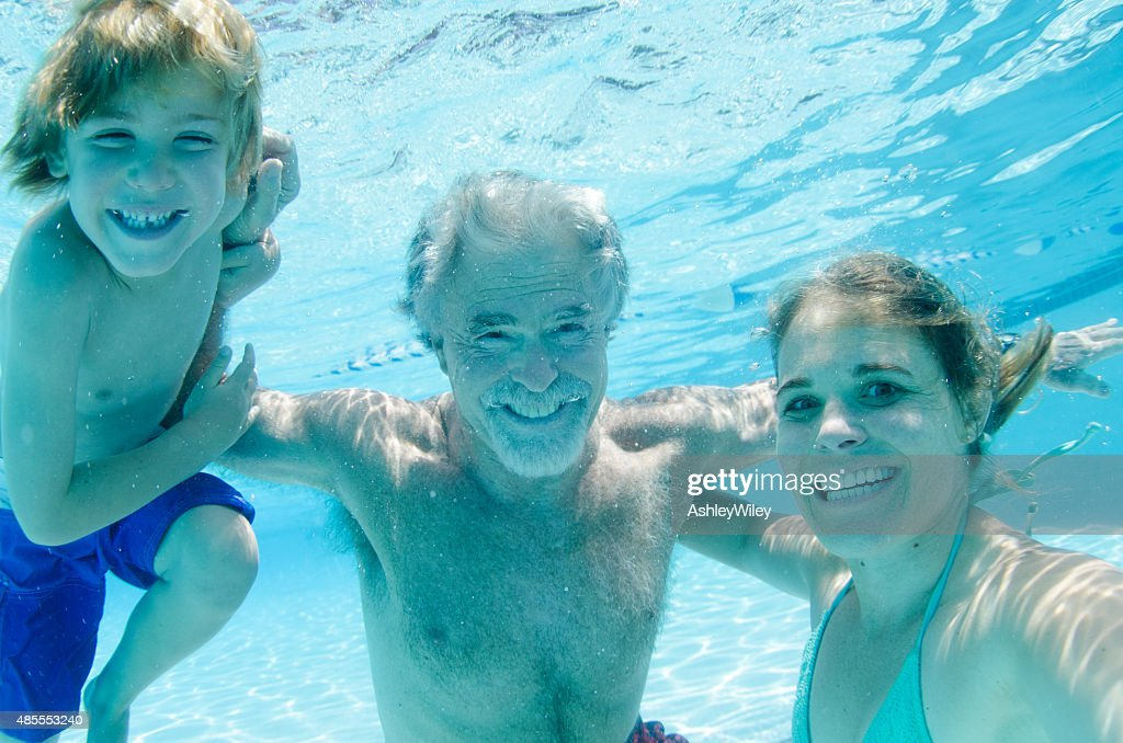 Grandpa, mother, and son swimming together, underwater smiling : Stock Photo