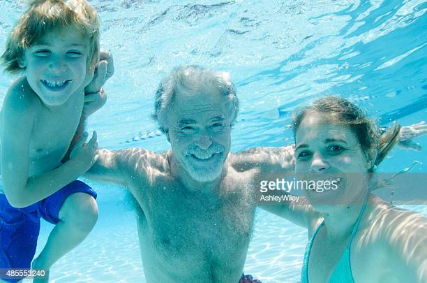 Grandpa, mother, and son swimming together, underwater smiling
