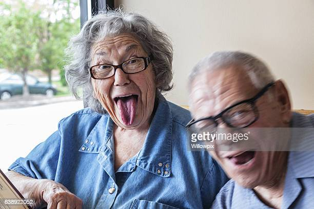 grandpa photo bombing grandma making funny tongue wagging face - fat woman funny stock photos and pictures