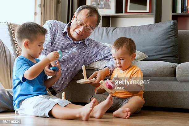 Grandpa playing with grandsons (4-5 years, 2-3 years)