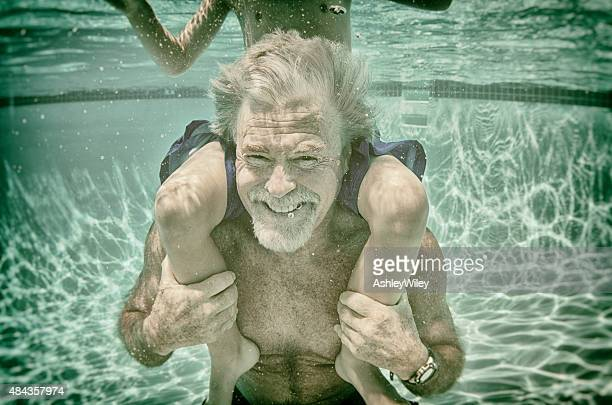 Grandpa plays with his grandson underwater in a pool in summer