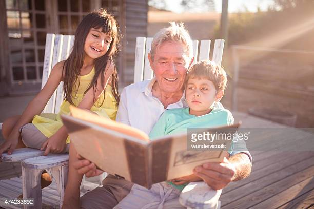 Grandpa reading a story to his grandkids outdoors