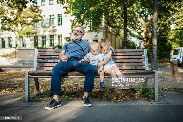 grandpa sitting on bench with grandchildren - bench stock pictures, royalty-free photos & images