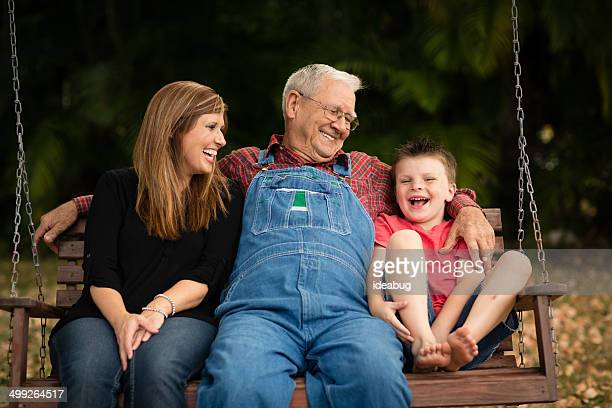 grandpa swinging with his granddaughter and great grandson - great granddaughter stock photos and pictures