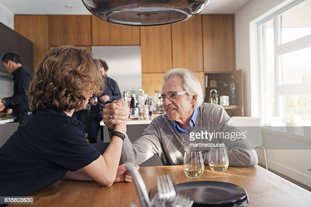Grandpa taking grandson to arm wrestling challenge after family dinner.