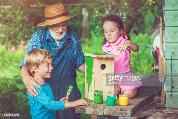Grandpa with children make and paint birdhouse