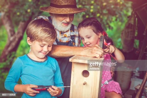 Grandpa with children make birdhouse