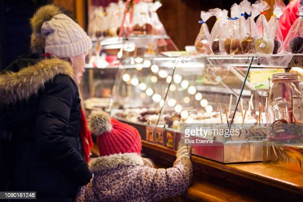 grandparent and child looking at chocolates on display at a german christmas market stall - chocolate shop stock pictures, royalty-free photos & images