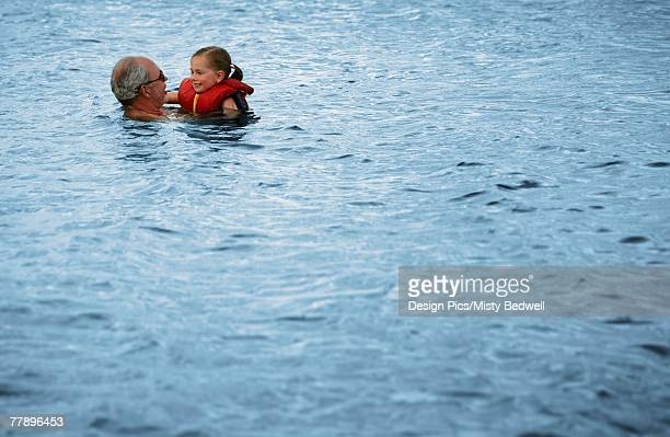 grandparent swimming with grandchild - reddingsvest stockfoto's en -beelden