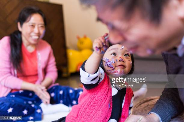 Grandparents and child having fun with paint on her face