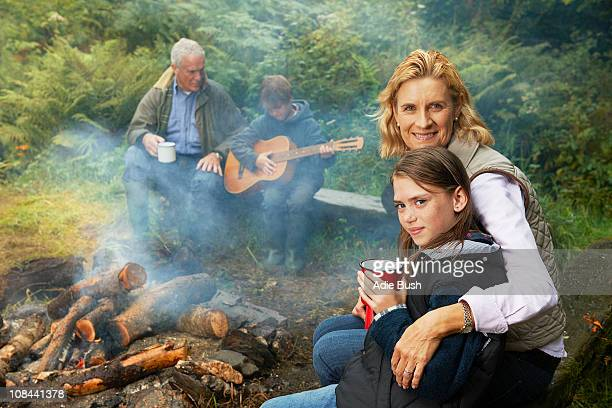Grandparents and children by camp fire