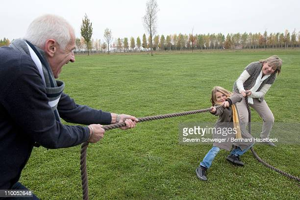Grandparents and girl playing tug-of-war