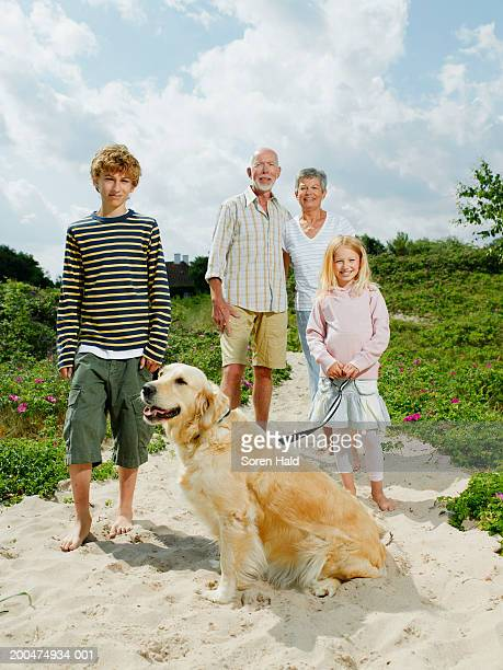 Grandparents and grandchildren (7-11) and dog on beach, smiling