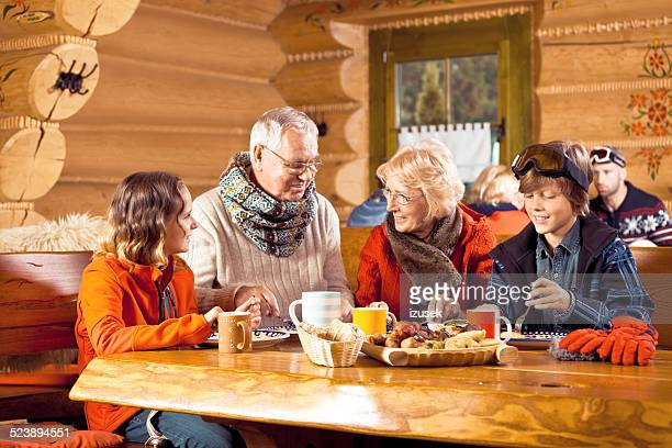 Grandparents and grandchildren having lunch after skiing