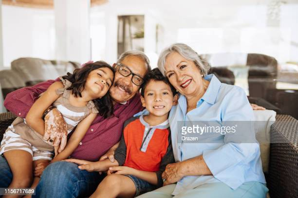 grandparents and grandchildren - latin/hispanic family together. - family at home stock photos and pictures