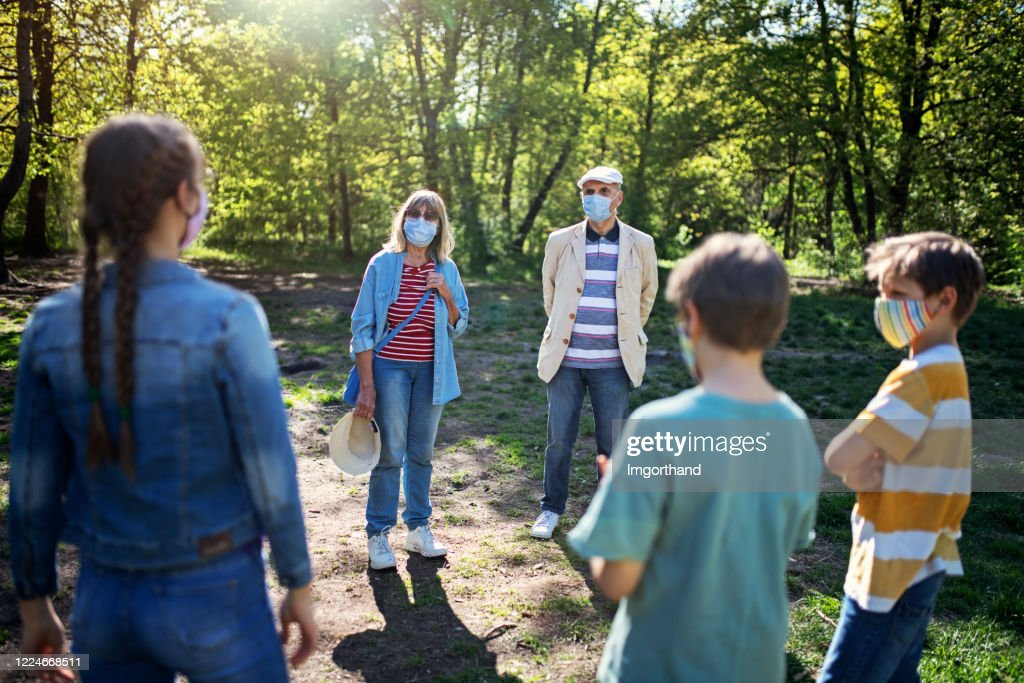 Grandparents and grandchildren meeting in park during COVID-19 pandemic : Stock Photo