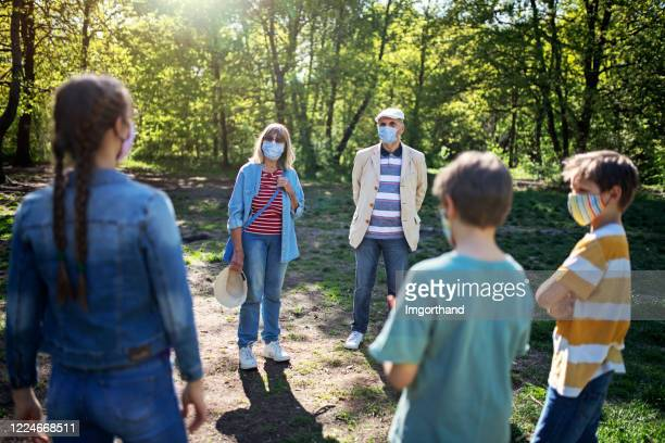 grandparents and grandchildren meeting in park during covid-19 pandemic - social distancing stock pictures, royalty-free photos & images