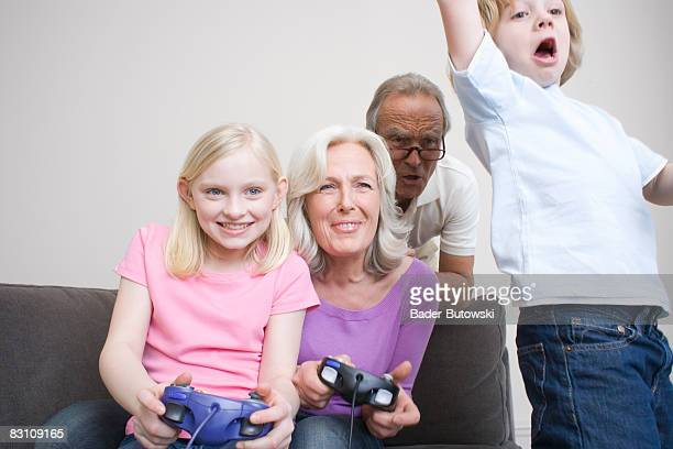Grandparents and grandchildren (8-9) playing video game