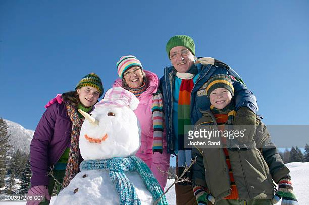 Grandparents and grandchildren (9-13) standing by snowman, smiling