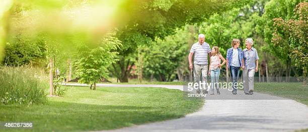 grandparents and grandchildren walking at park - panoramic stock pictures, royalty-free photos & images