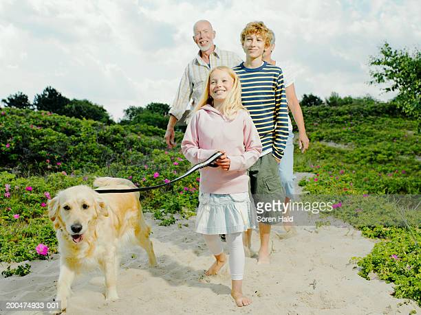 Grandparents and grandchildren (7-11) walking dog on beach, smiling