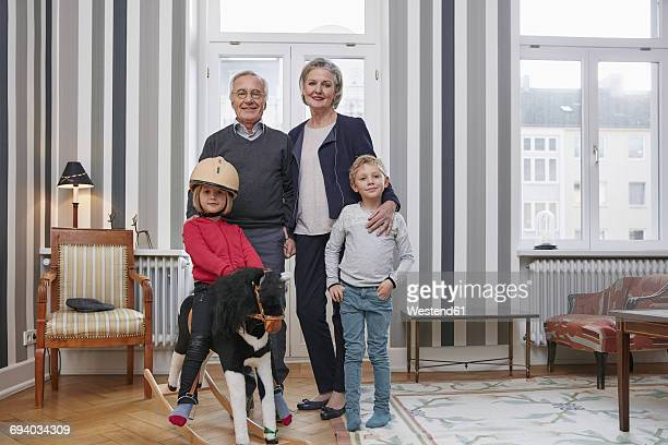 Grandparents and grandchildren with rocking horse in living room