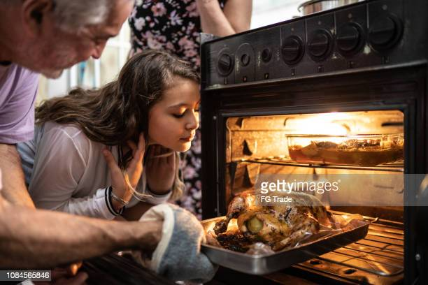 grandparents and granddaughter checking the traditional turkey for christmas dinner - turkey meat stock pictures, royalty-free photos & images