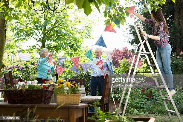 Grandparents and granddaughter hanging up bunting
