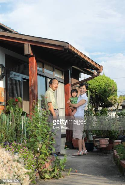 grandparents and granddaughter looking at here in front of entrance - 建物入口 ストックフォトと画像