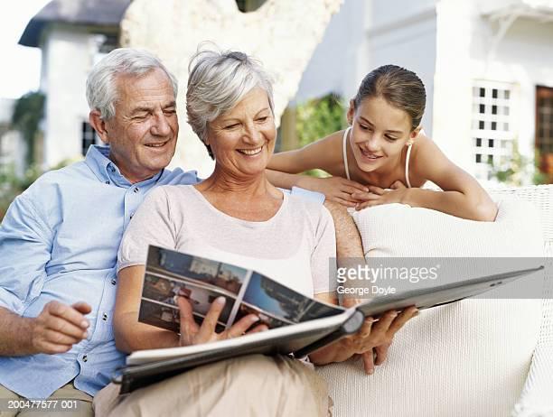 Grandparents and granddaughter (12-14) looking at photo album, smiling