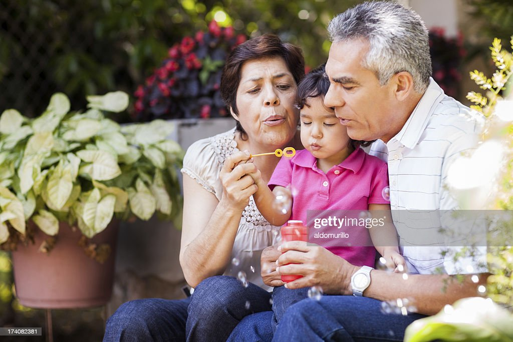 Grandparents and granddaughter making bubbles : Stock Photo