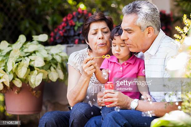 grandparents and granddaughter making bubbles - latin american and hispanic ethnicity stock pictures, royalty-free photos & images