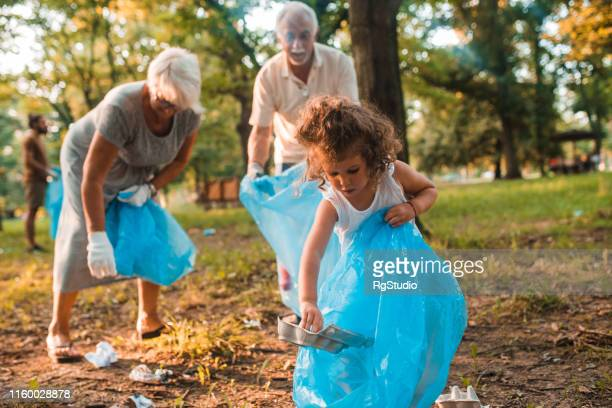 grandparents and granddaughter recycling - selfless stock pictures, royalty-free photos & images