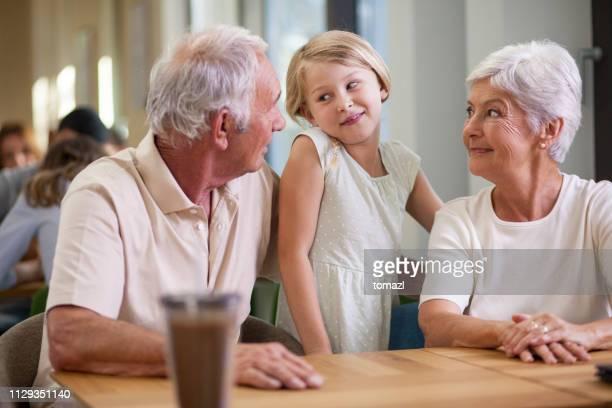 grands-parents et petite-fille de passer du temps dans le café-restaurant - femme entre deux hommes photos et images de collection