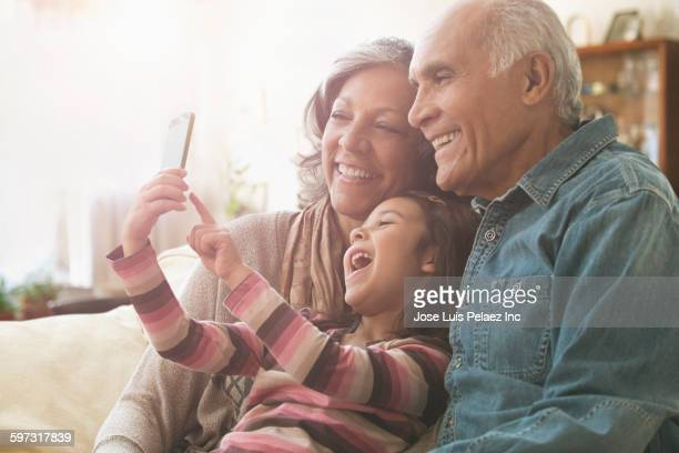 Grandparents and granddaughter taking selfie on sofa